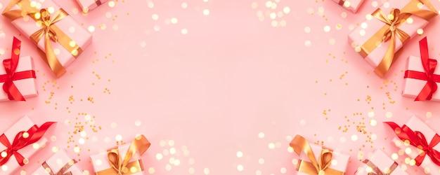 Carte de voeux joyeux noël et bonne année avec boîte-cadeau en papier, noeud de ruban d'or sur fond rose.