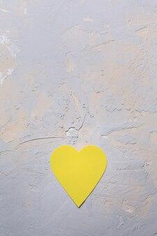 Carte de voeux minimaliste de saint valentin dans les couleurs ultimes gris et jaune lumineux, coeur de papier sur fond texturé, mise à plat
