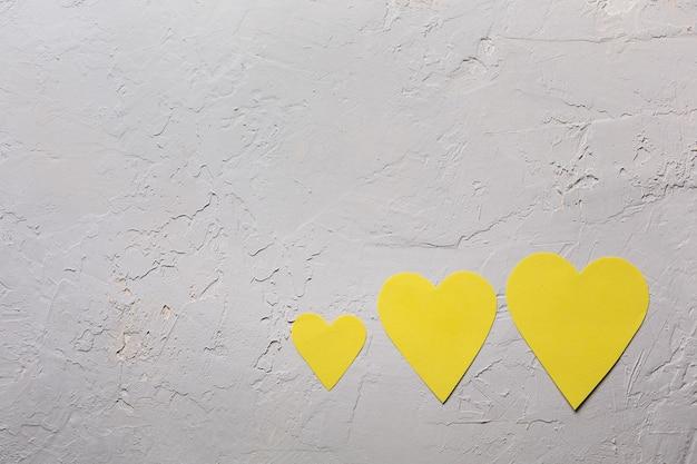 Carte de voeux minimaliste de saint valentin dans les couleurs ultimes gris et jaune lumineux, trois coeurs de papier sur fond texturé, mise à plat