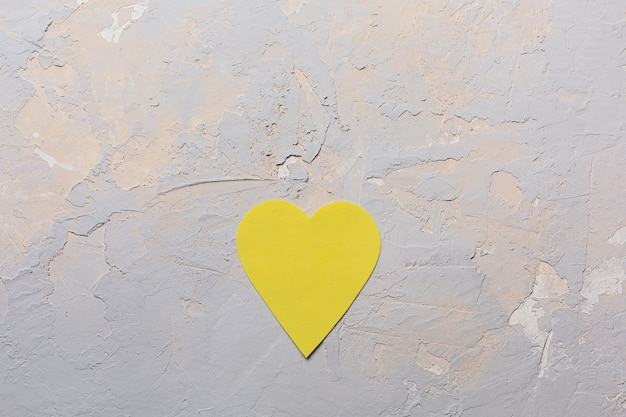 Carte de voeux minimaliste saint valentin en pantone 2021 couleurs gris et jaune, coeur de papier sur fond texturé, mise à plat