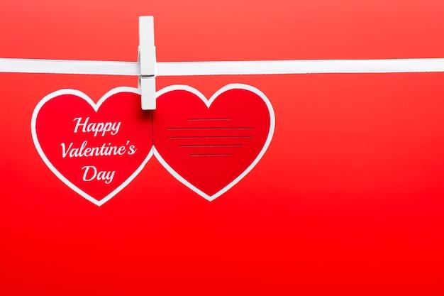 Carte de voeux avec des mots de bonne saint-valentin épinglés sur une corde sur le fond rouge.