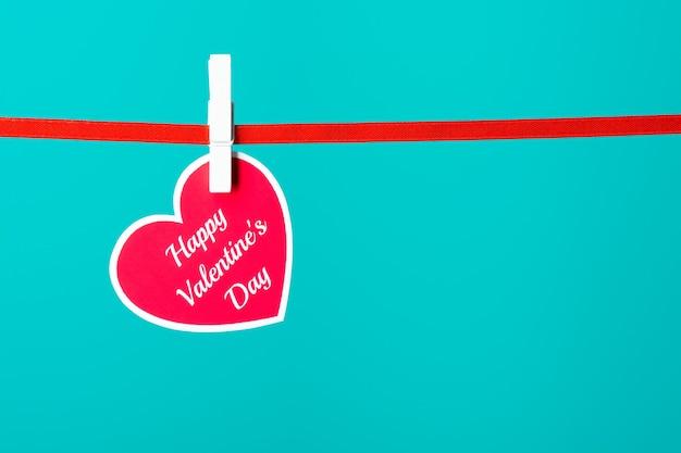 Carte de voeux avec des mots de bonne saint-valentin épinglés sur une corde sur le fond turquoise.