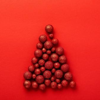 Carte de voeux de noël avec arbre de noël fait de boules de jouets rouges décorées de confettis dorés dans une enveloppe rouge sur rouge.