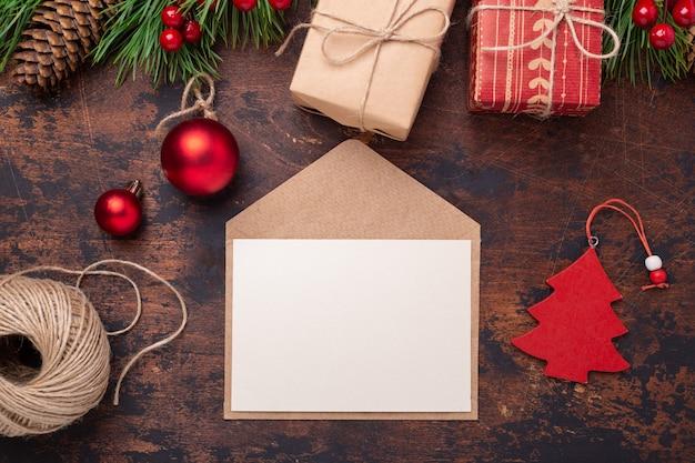 Carte de voeux de noël avec une branche de sapin, des cadeaux, une boîte présente et une enveloppe. fond en bois vue de dessus