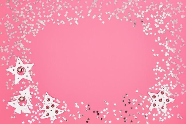 Carte de voeux de noël. décorations de noël blanches et argentées sur fond rose vif. espace de copie, vue de dessus. mise à plat, noël, hiver, concept de nouvel an.