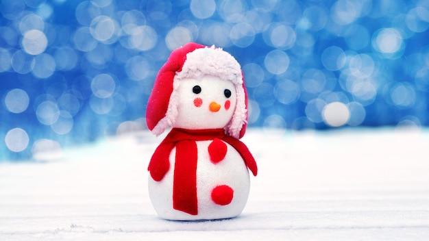 Carte de voeux de noël et du nouvel an avec bonhomme de neige à l'extérieur et bokeh en arrière-plan