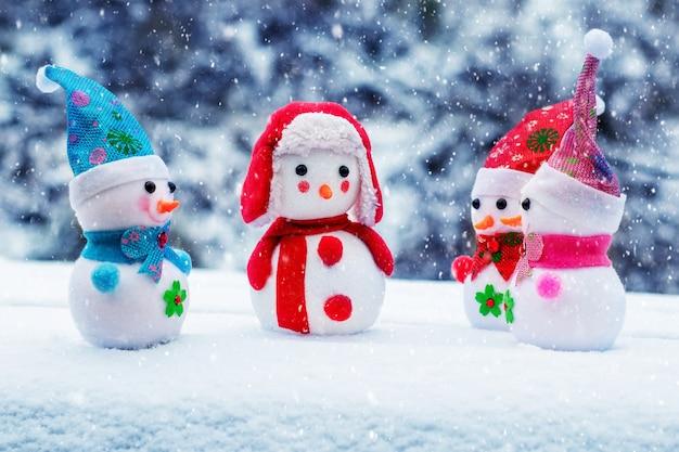 Carte de voeux de noël et du nouvel an avec des bonhommes de neige à l'extérieur pendant les chutes de neige