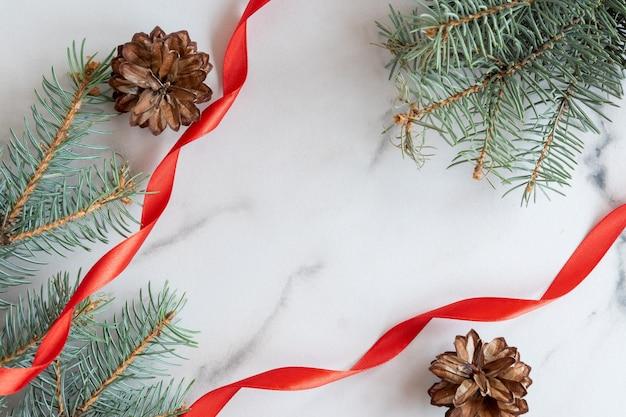 Carte de voeux de noël et du nouvel an avec espace de copie. branches de conifères bleus, cônes et ruban de satin rouge disposés sur fond de marbre blanc