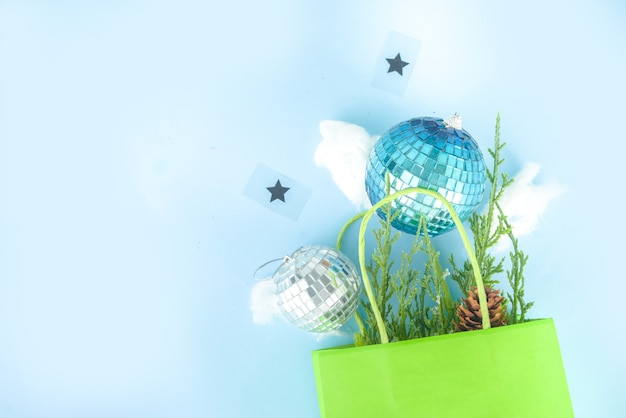 Carte de voeux de noël simple, invitation à une fête, vente flatlay abstraite avec boules de noël disco, branches de sapin, sac en papier avec noeud festif, sur fond bleu clair vue de dessus de l'espace de copie