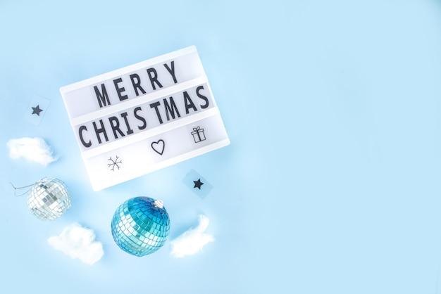 Carte de voeux de noël simple, invitation à une fête, vente flatlay abstraite avec boules de noël disco et tableau lumineux, sur fond bleu clair vue de dessus de l'espace de copie