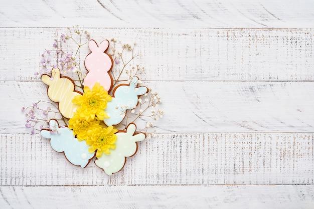 Carte de voeux de pâques avec des lapins colorés, des œufs, des poulets et des carottes biscuits en pain d'épice sur fond vieux en bois blanc avec espace de copie. vue de dessus.
