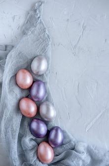 Carte de voeux de pâques avec des oeufs de pâques colorés sur fond gris. vue de dessus avec un espace pour votre texte.