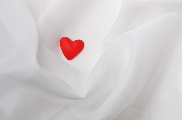 Carte de voeux pour la saint-valentin. coeur rouge sur un tissu blanc