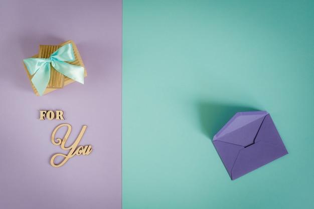 Carte de voeux pour vous sur un fond violet - menthe avec des coffrets cadeaux et une enveloppe.