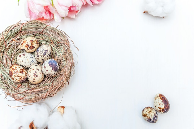 Carte de voeux de printemps. oeufs de pâques en coton nid et bouquet de fleurs de tulipes fraîches roses sur fond de bois blanc rustique