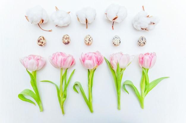 Carte de voeux de printemps. oeufs de pâques en coton et rose bouquet de fleurs de tulipes fraîches sur fond de bois blanc rustique