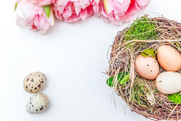 Carte de voeux de printemps. oeufs de pâques en nid et bouquet de fleurs de tulipes fraîches roses sur fond de bois blanc rustique