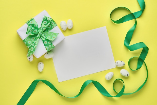 Carte de voeux de printemps de pâques avec boîte-cadeau avec ruban vert, oeufs et carotte sucrée sur table rose avec place pour le texte. vue de dessus.