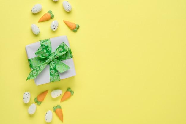 Carte de voeux de printemps de pâques avec boîte-cadeau avec ruban vert, oeufs et carotte sucrée sur table rose. vue de dessus.