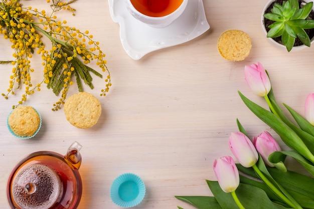 Carte de voeux de printemps avec tulipes, mimosa, thé et cupcakes sur table en bois.
