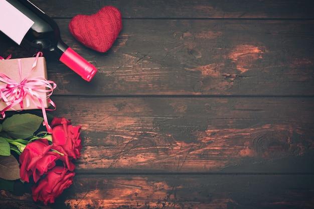 Carte de voeux romantique saint valentin. fleurs roses rouges, bouteille de vin, coffret cadeau et coeur décoratif sur table en bois. espace libre.