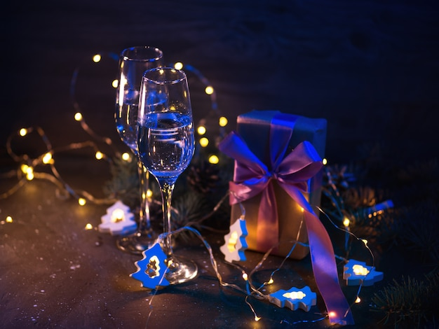 Carte de voeux romantique de soirée de noël. deux verres de champagne, coffret cadeau, décor de vacances aux couleurs éclatantes
