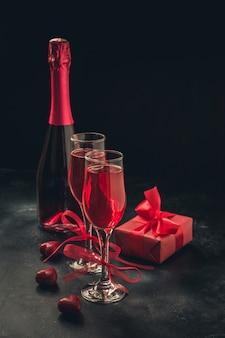 Carte de voeux saint valentin et anniversaire avec champagne et bonbons coeur sur fond noir.