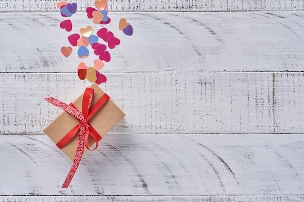 Carte de voeux saint valentin avec boîte-cadeau et guirlandes devant un mur en bois blanc. vue de dessus.