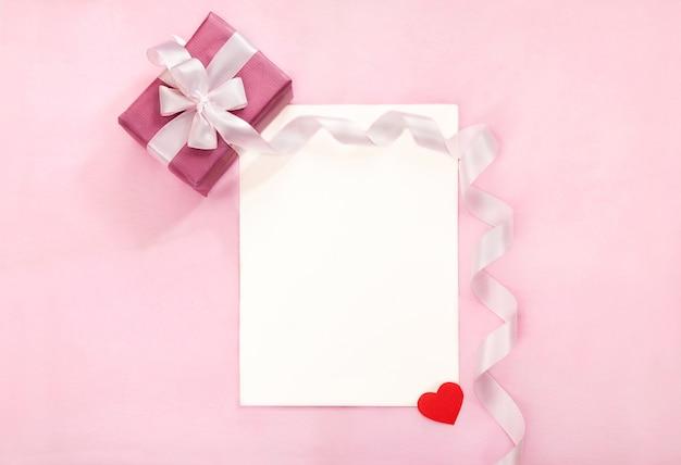 Carte de voeux saint valentin avec boîte-cadeau rose, arc blanc, long ruban courbé et coeur rouge en papier