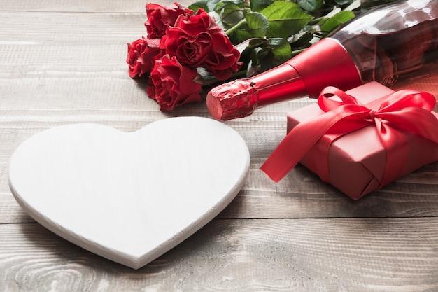 Carte de voeux saint valentin avec bouquet de fleurs roses rouges, une bouteille de champagne et un coffret cadeau sur une table en bois. copiez l'espace.