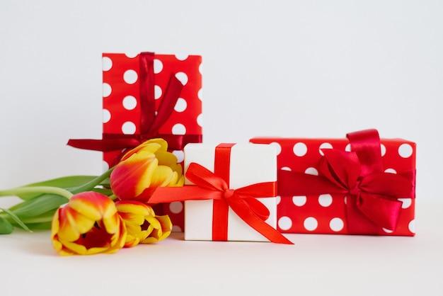 Carte de voeux de la saint-valentin. cadeaux rouges et blancs avec des rubans et des nœuds et un bouquet de tulipes rouges et jaunes