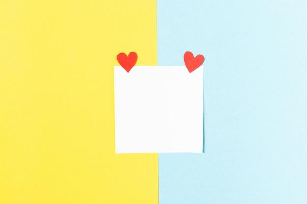 Carte de voeux saint valentin carré blanc pour les notes avec des coeurs rouges sur fond bleu et jaune
