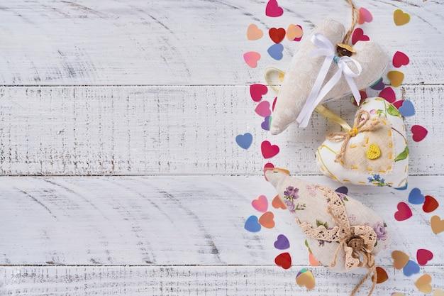 Carte de voeux saint valentin avec des coeurs faits à la main devant un mur en bois blanc. vue de dessus.