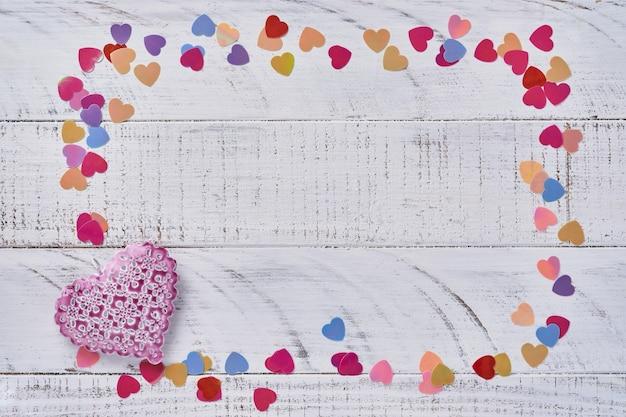 Carte de voeux saint valentin avec des coeurs roses faits à la main devant un mur en bois blanc. vue de dessus.