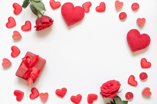 Carte de voeux saint valentin. composition avec cadeau, roses, coeurs rouges sur blanc. vue de dessus. copiez l'espace.