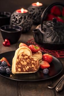 Carte de voeux saint valentin avec de délicieuses crêpes en forme de coeur, thé vert, théière noire, bougies et roses. concept de la saint-valentin