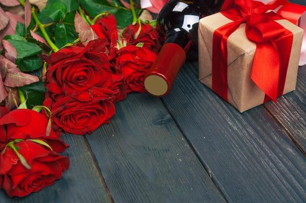 Carte de voeux saint valentin. fleurs rose rouge, vin et coffret cadeau sur une table en bois.