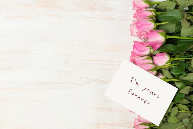 Carte de voeux de saint-valentin avec des fleurs roses sur fond en bois. vue de dessus avec espace de copie