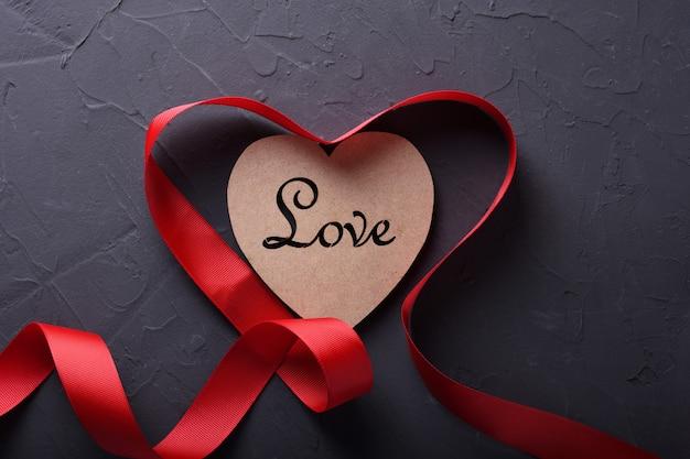 Carte de voeux saint valentin fond symboles d'amour, décoration rouge avec coeur sur fond de pierre. vue de dessus avec espace de copie et texte.