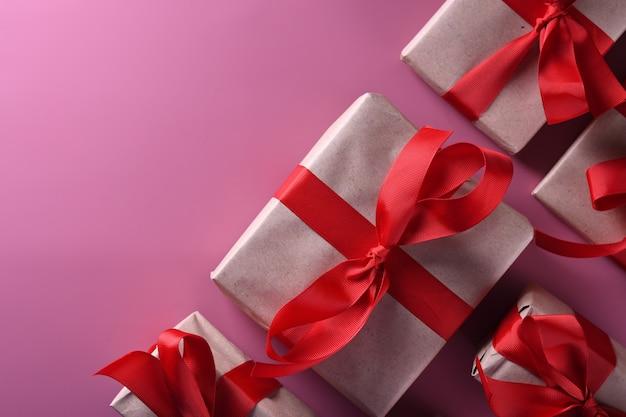 Carte de voeux saint valentin fond symboles d'amour, décoration rouge avec des coffrets cadeaux sur fond rose. vue de dessus avec espace de copie et texte.