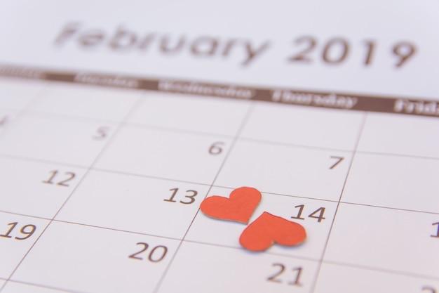 Carte de voeux saint valentin. papier coeurs rouges sur la page de calendrier le 14 février avec espace de copie