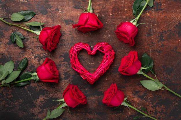 Carte de voeux saint valentin. roses rouges et coeur textile décoratif sur table en pierre. vue de dessus.