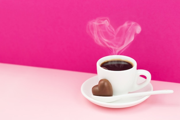 Carte de voeux saint valentin. tasse de café et coeur en chocolat sur fond rose
