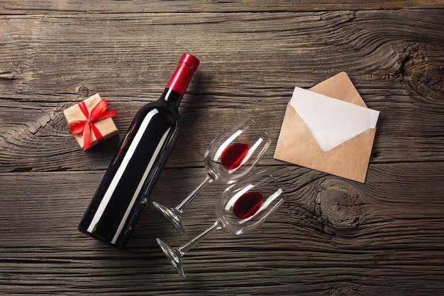 Carte de voeux saint valentin. vin rouge, coffret cadeau et verres sur la table en bois. voir avec un espace pour vos salutations.