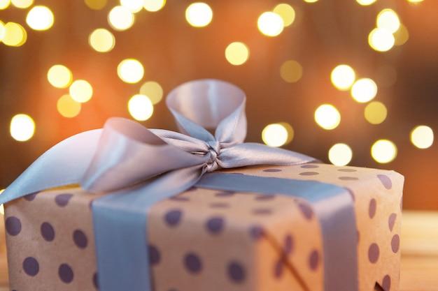 Carte de voeux de vacances avec des boîtes-cadeaux contre les lumières brouillées