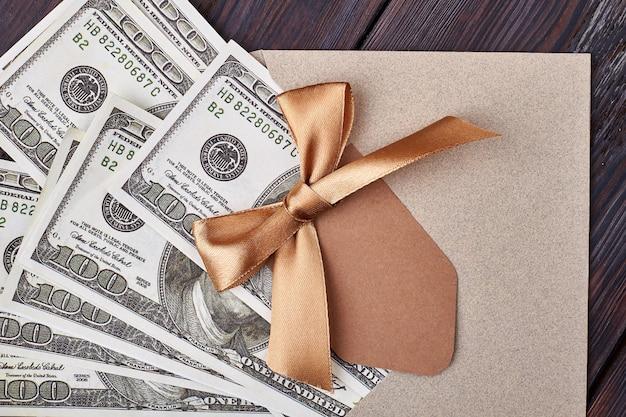 Carte de voeux vierge et dollars. noeud de ruban sur enveloppe. l'argent comme idole moderne.