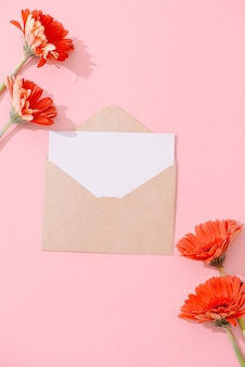 Carte de voeux vierge avec enveloppe brune et fleur de gerbera sur table rose avec ton vintage et vignette