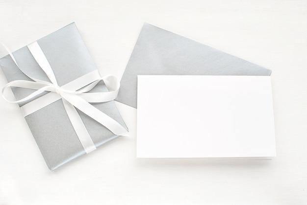 Carte de voeux vierge, invitation avec enveloppe argentée et cadeau pour noël.