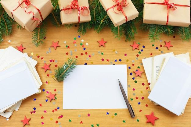Carte de voeux vierge de noël avec des coffrets cadeaux entourés de décorations de noël.