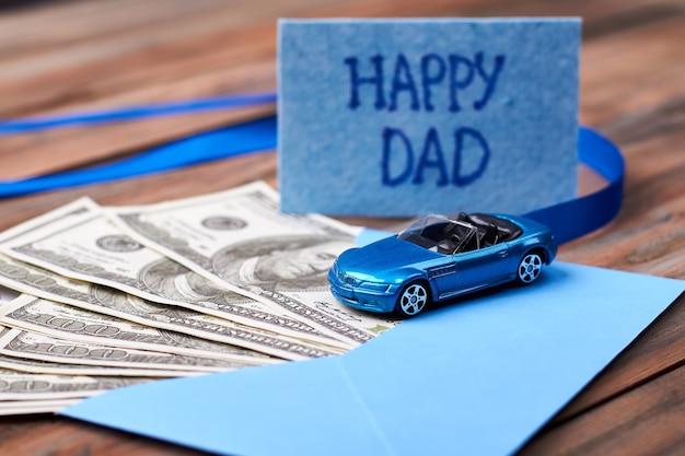 Carte et voiture de papa heureux. ruban et enveloppe avec de l'argent. cadeau précieux pour papa.